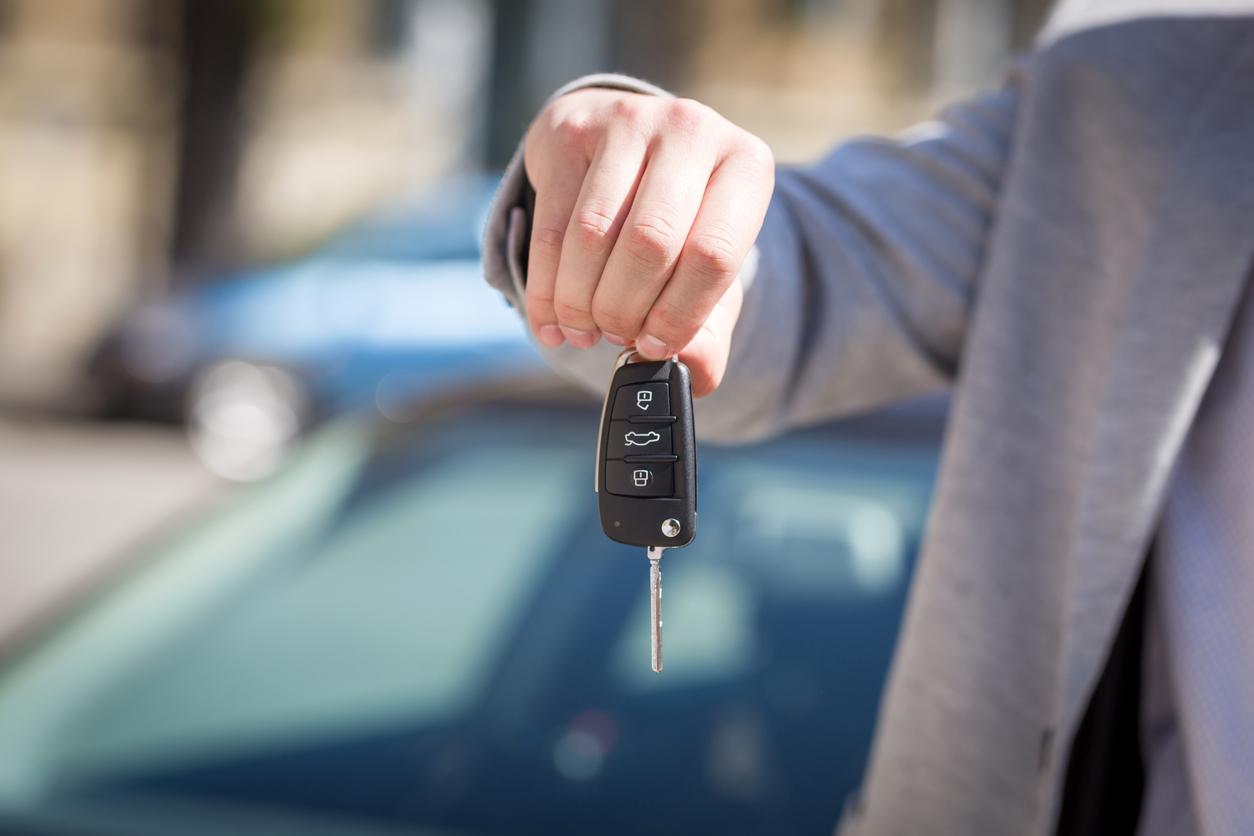 main d'homme tenant une clé de voiture
